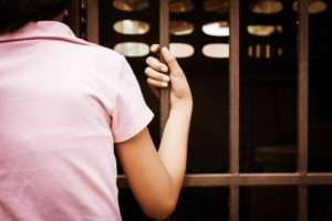 girl holding jail bars
