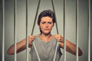 desperate woman bending bars of her prison cell