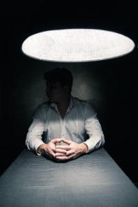 man in a dark room with spotlight