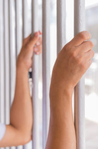Hands of man holding jail bars