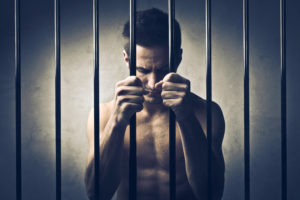 naked man behind bars