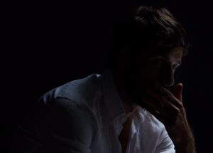 sad man sitting in the dark