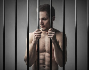 shirtless man behind bars