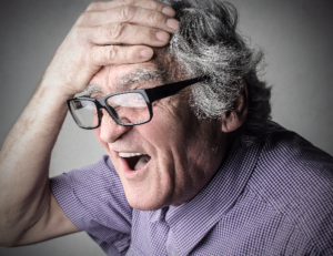 shocked elderly man holding his head