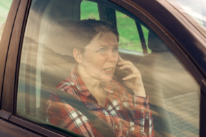 woman talking on the phone inside her car